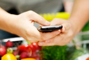 Woman grocery shopping with mobile phone